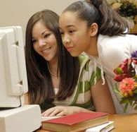 Two girls looking at a computer screen.